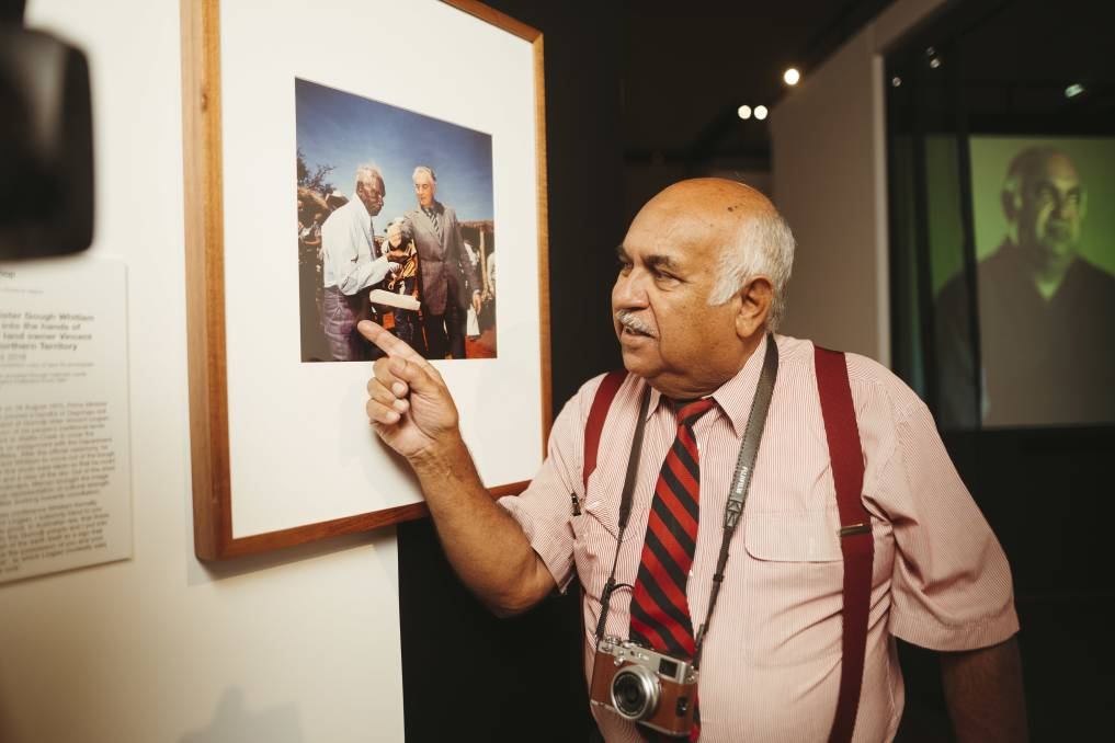 Photographer Mervyn Bishop at the National Film and Sound Archive of Australia with the photo he took of then-prime minister Gough Whitlam and Vincent Lingiari. Picture: Dion Georgopoulos