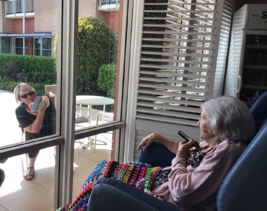 Connecting: Shona Bobbins (outside) interacts with her mum Gwen Wood through a window at the aged care centre. Gwen's other daughter Meryl was also present. Photo: supplied.