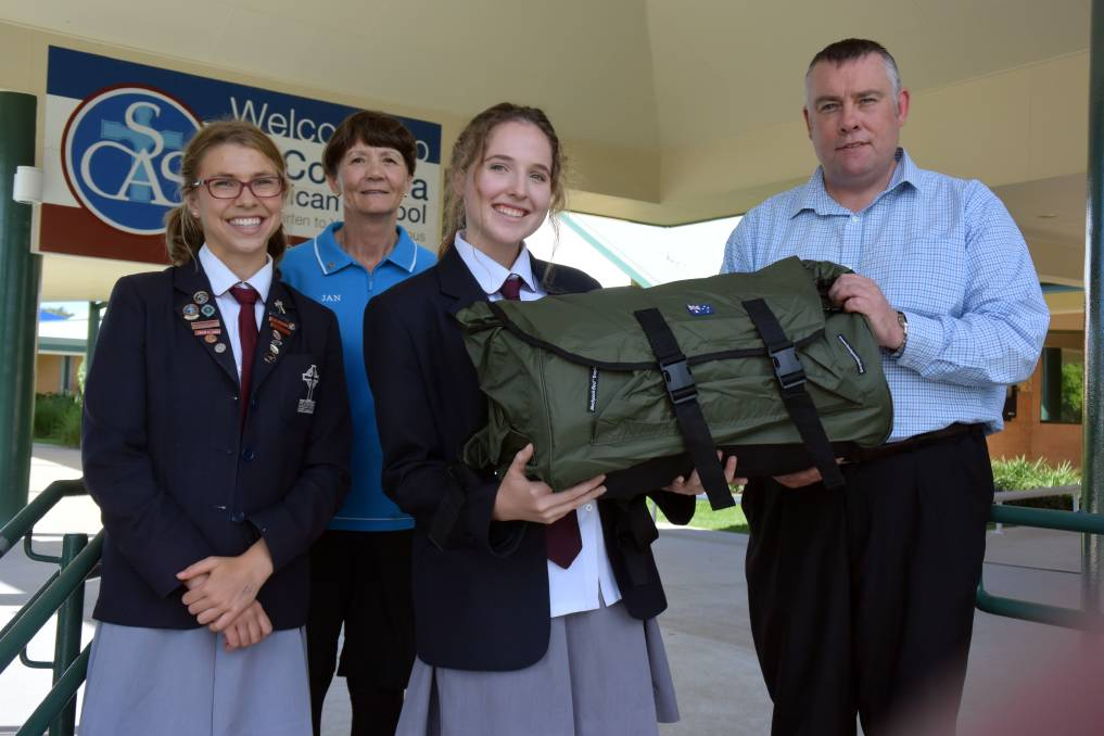 A worthy cause: St Columba Anglican School captain Madeleine Brown and interact president Emma Dennis present New Horizons representative Darryl Barleycorn and Rotary Sunrise Port Macquarie member Jan Crombie with a swag to help the homeless.